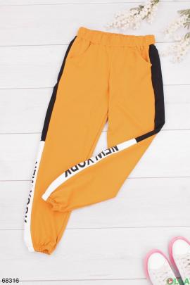 Женские оранжевые спортивные брюки с надписью